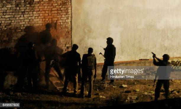 Police officers make a hole in a wall of the building where the suspect was hiding to send in optical fibre cameras around 300 police personnel...