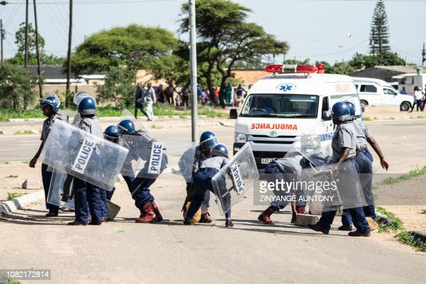 Police officers make way for an ambulance by removing stones from a barricade during a stayaway demonstration against the doubling of fuel prices on...