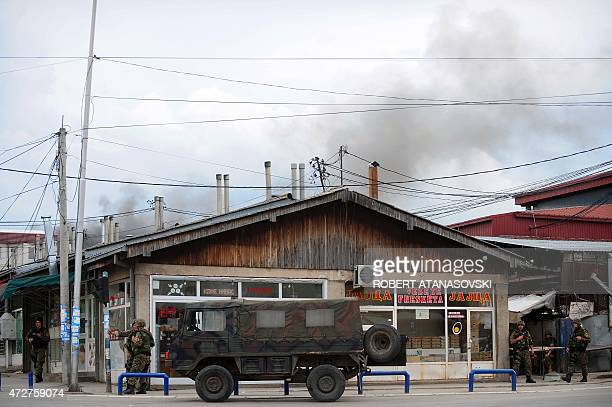 Police officers man a checkpoint in the conflict zone as black pillar of smoke is visible behind them in Kumanovo northern Macedonia on May 9 2015...