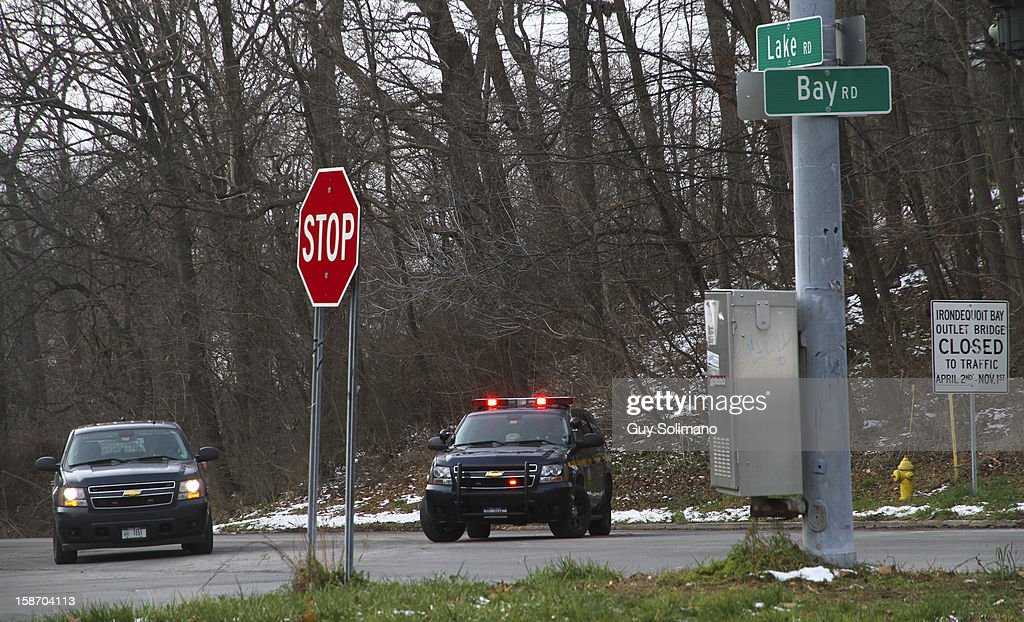 Police officers man a road block on Lake Road following two firefighters killed, and two injured in a presumed ambush attack December 24, 2012 in Webster, New York. Authorities say an ex-con gunned down two firefighters after setting a car and a house on fire early Monday, then took shots at police and committed suicide while several homes burned.