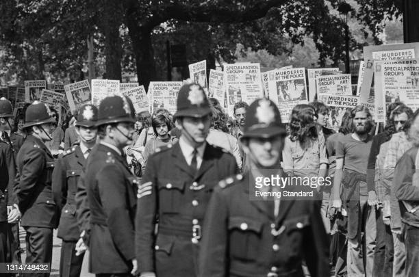 Police officers march alongside placards with the accusation 'Murdered By The Police' at a silent march by the NUS after the death of Kevin Gately,...