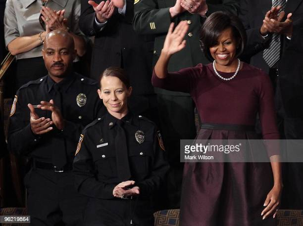 Police Officers Mark Todd and Kimberly Munley of Killeen TX look on as US first lady Michelle Obama waves to the chamber before US President Barack...