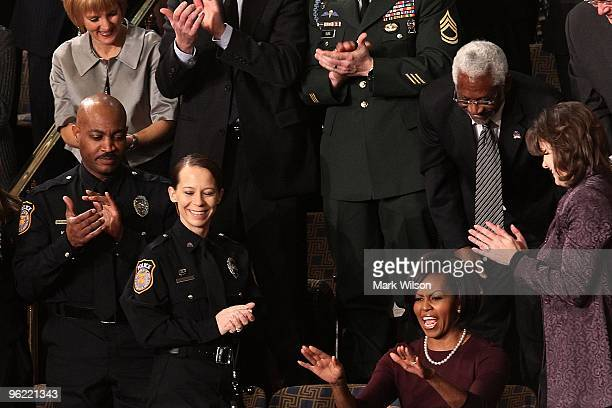 Police Officers Mark Todd Kimberly Munley of Killeen TX and Haitian Ambassador to the United States Raymond Joseph look on as US first lady Michelle...