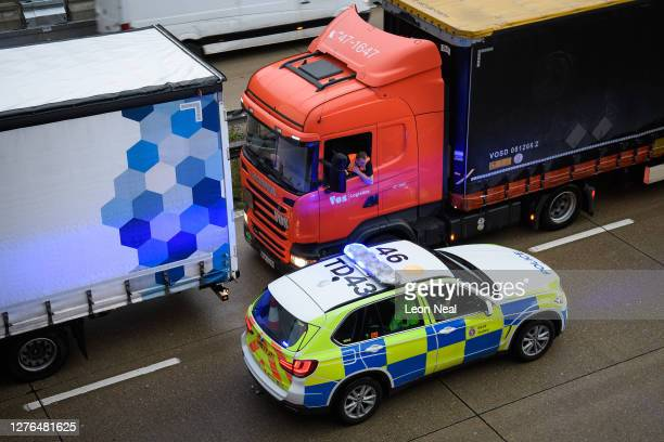 Police officers marshall the heavy goods vehicles as they queue along the M20 motorway as part of the Operation Stack traffic control plan, on...