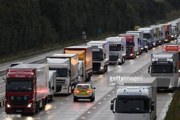 Police officers marshall the heavy goods vehicles as they queue along the M20 motorway as part of the Operation Stack traffic control plan on...