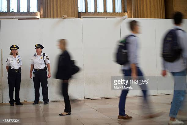 Police officers monitor activity as commuters walk past at 30th Street Station as Amtrak resumes northbound service after last week's derailment on...