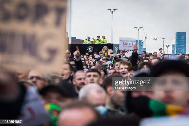 Police officers monitor football fans during a protest against the Glazer's ownership of Manchester United.