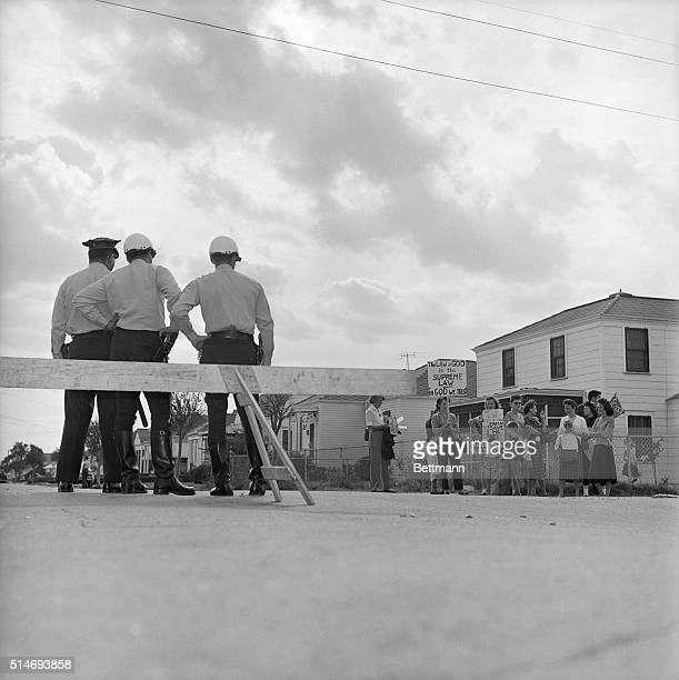 Police officers monitor protesters from a roadblock set up one block from William Franz Elementary School in New Orleans Louisiana where African...