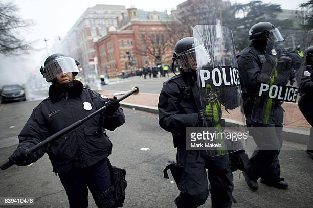 Police officers motion protestors away from a limousine is set aflame with We the People spray painted on the side after the inauguration of Donald...