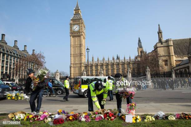 Police officers move floral tributes from outside the Houses of Parliament to Parliament Square following Wednesday's attack on Westminster on March...