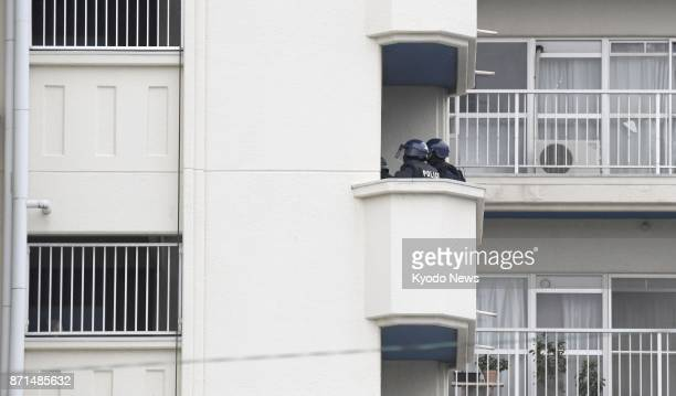 Police officers move in at an apartment building in Kitakyushu Fukuoka Prefecture on Nov 8 where a man in his 60s holed himself up after shooting his...