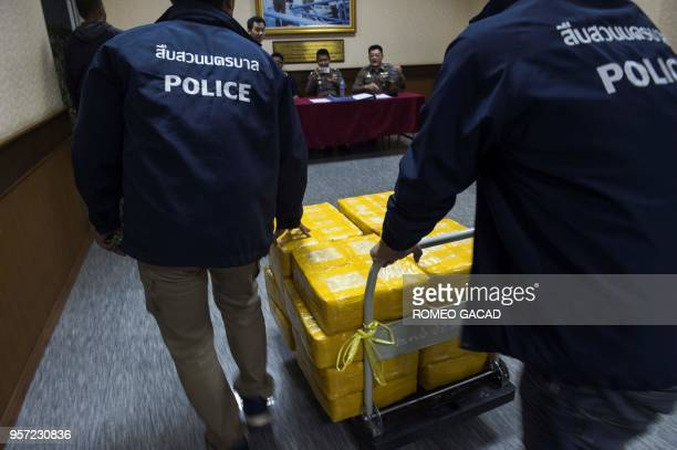 Police officers move seized drugs after a press conference in Bangkok on May 11 2018 Ten million madeinMyanmar 'yaba' pills and nearly half a tonne...