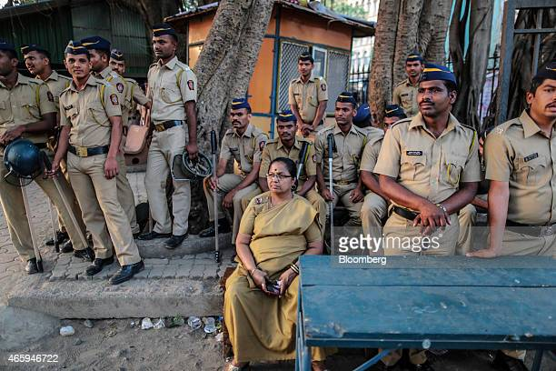 Police officers observe butchers and traders unseen during a protest against the ban of beef organized by by the Sarv Shramik Sangh the trade union...