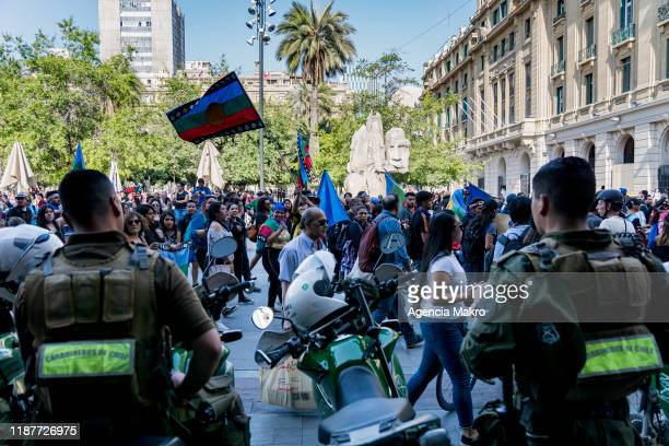 Police officers observe the Mapuche demonstrators at Plaza de Armas during a protest against president Sebastian Piñera to commemorate the first...