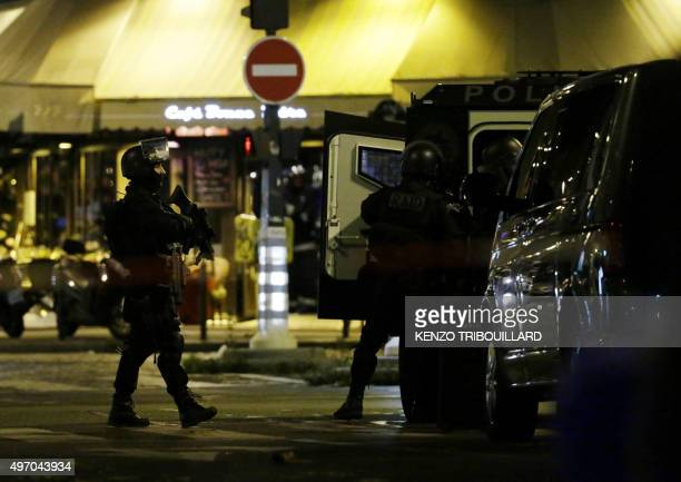 Police officers of the armed response unit man a position close to the Cafe Bonne Biere in Paris on November 13 2015 after a series of gun attacks...