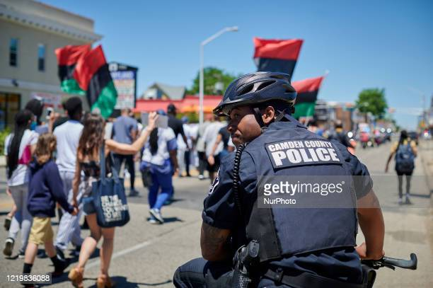 Police officers of the Camden County Police Department keep an eye out as demonstrators take part in a Black Lives Matter protest march in Camden, NJ...