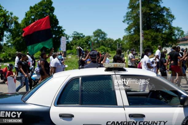 Police officers of the Camden County Police Department keep an eye out as demonstrators take part in a Black Lives Matter protest march in Camden NJ...