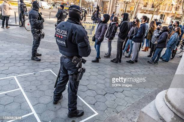 Police officers of the Mossos d'Esquadra of Catalonia are seen holding back anti-fascist militants away from the information tent of the far-right...