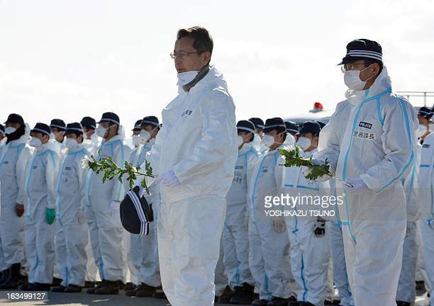 Police officers offer chrysanthemum flowers for tsunami victims in Namie near the striken TEPCO's Fukushima Daiichi nuclear plant in Fukushima...