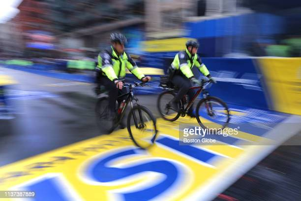 Police officers on bikes cross the finish line as they ride into their positions along the course of the 123rd Boston Marathon on April 15 2019