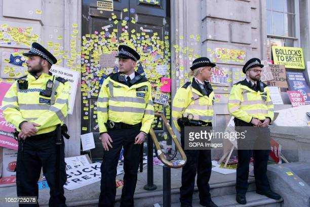 Police officers on guard at the Cabinet office building entrance to prevent antiBrexit protesters from sticking stickers around the entrance during a...
