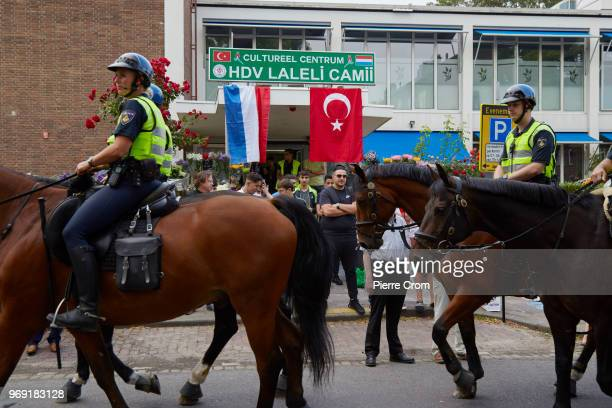 Police officers on horses pass by the Laleli Mosque on June 7 2018 in Rotterdam NetherlandsThe antiIslam group Pegida plans to roast pigs on a...