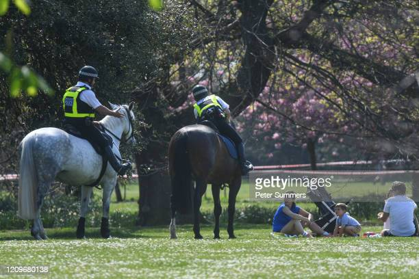 Police officers on horses speak to a family having a picnic in Greenwich Park on April 11, 2020 in London, England. Public Easter events have been...