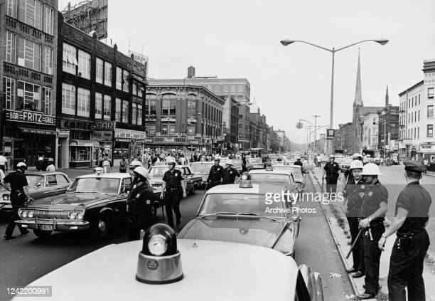 Police officers on Lenox Avenue, near 125th Street in Harlem, New York City, during a period of rioting sparked by the killing of African American...