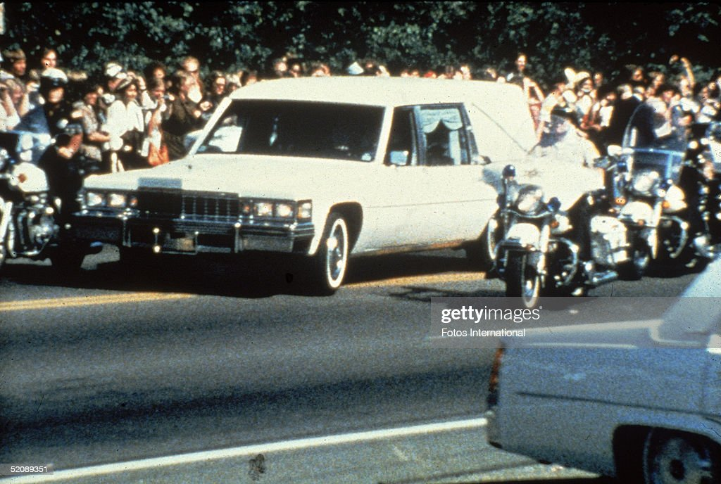 Police officers on motorcycles escort a white hearse containing the body of American rock and roll singer Elvis Presley as it heads towards the funeral past crowds of people who line the streets to watch, Memphis, Tennessee, August 18, 1977.