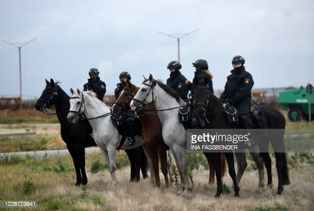 Police officers on their horses stand nest to a mass action of climate activists aiming to block huge openpit coal mine Garzweiler on September 26...