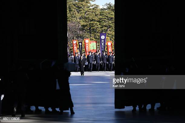 Police officers open the gate as wellwishers walk towards the Imperial Palace to listen to an address by Emperor Akihito and greet the Japanese Royal...