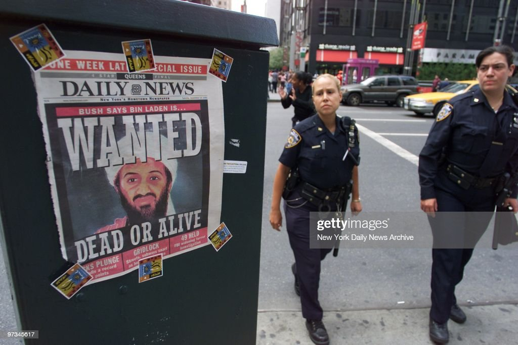 Police officers pass a Daily News cover showing a picture of Osama Bin Laden, who's been called the prime suspect in the terrorist attack on the World Trade Center. The headline reads: Wanted Dead or Alive.,