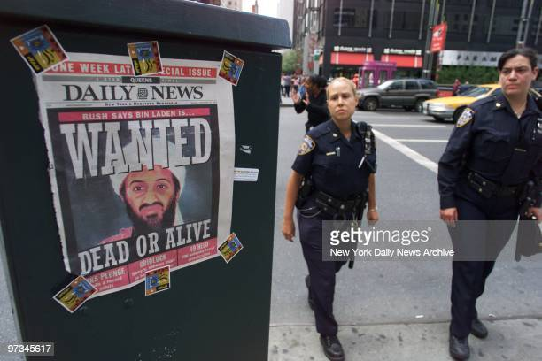 Police officers pass a Daily News cover showing a picture of Osama Bin Laden who's been called the prime suspect in the terrorist attack on the World...
