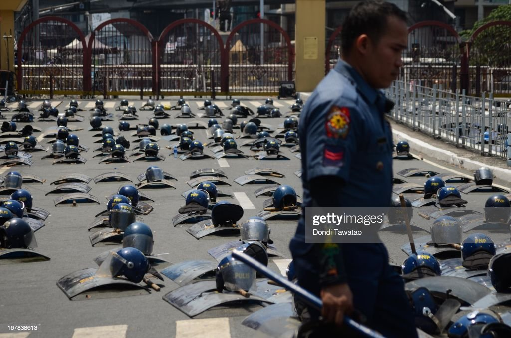 Police officers pass by rows of shields and helmets near the presidential palace on May 1, 2013 in Manila, Philippines. Philippines workers unions gather in the streets of Manila to demand, among other things, better pay, an end to contractualization and lower prices of basic commodities. Labor day is celebrated across South East Asia on May 1st and is seen as an opportunity to acknowledge the social and economic accomplishments of the workers.