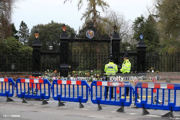 Police officers patrol a closed road as flowers are seen at the gates to Sandringham House on the royal Sandringham Estate in Norfolk on April 10,...