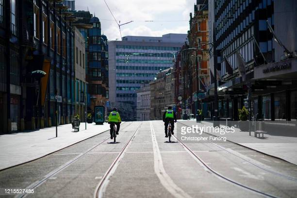 Police officers patrol a deserted Corporation Street in Birmingham city centre during the nationwide lockdown on March 29, 2020 in Birmingham, United...