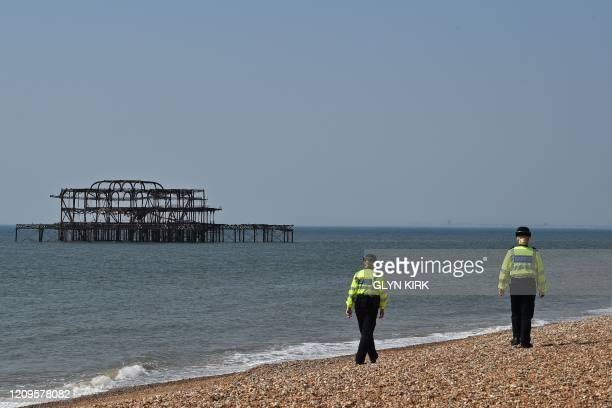 Police officers patrol a neardeserted beach in Brighton on the south coast of England on April 10 2020 as warm weather tests the nationwide lockdown...