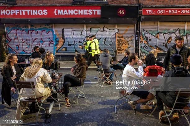 Police officers patrol as bars on Thomas Street in the Northern Quarter set out tables for customers on the closed road on July 04 2020 in Manchester...