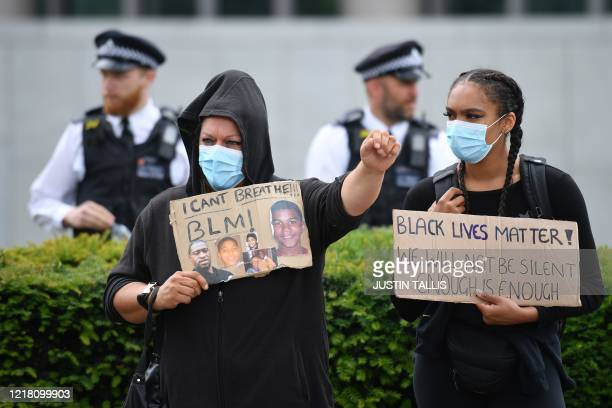 Police officers patrol as protesters wearing protective face masks stand with their placards ahead of a demonstration outside the US Embassy in...