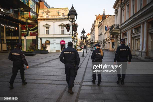 Police officers patrol at one of the main pedestrian Knez Mihailova street downtown Belgrade on March 30 as Serbia has introduced curfew from 5 pm to...