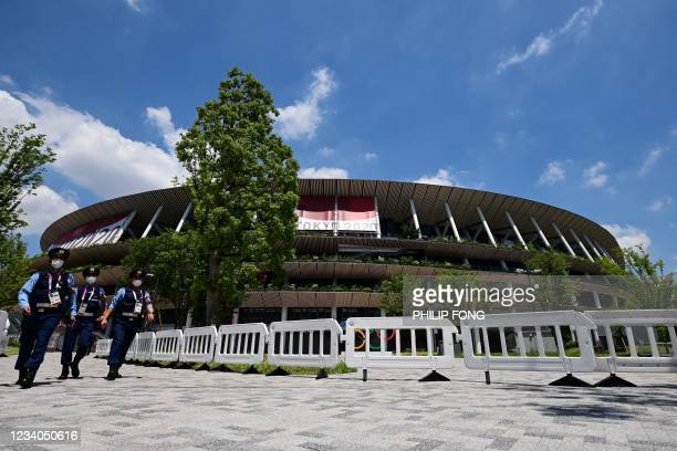 Police officers patrol at the Olympic Stadium, main venue of the Tokyo 2020 Olympic Games in Tokyo on July 19, 2021.