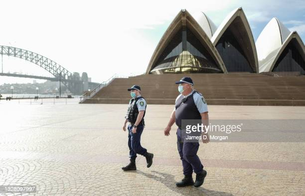 Police officers patrol at the Opera House on July 11, 2021 in Sydney, Australia. Lockdown restrictions have been tightened across NSW as COVID-19...