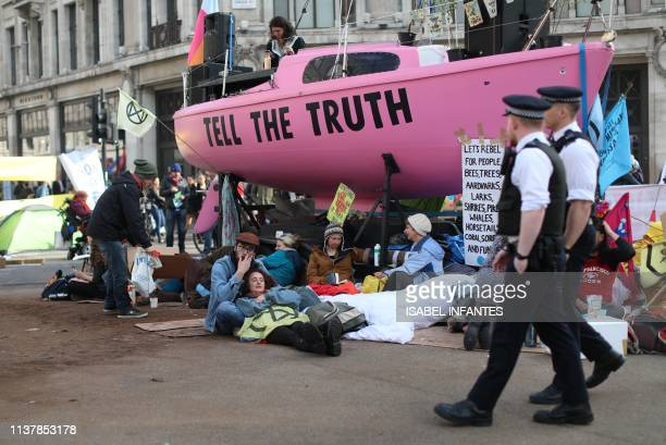 Police officers patrol by climate change activists occupying Oxford Circus in the busy shopping district of central London on April 18 2019 in the...