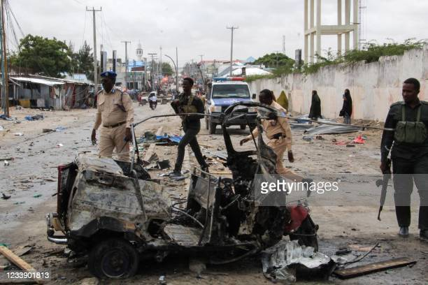 Police officers patrol by the wreckage of a car at the scene of suicide car bomb attack that targeted the city's police commissioner in Mogadishu, on...