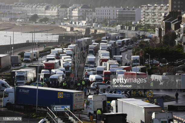 Police officers patrol in front of queues of vans and lorries at the Port of Dover on December 23, 2020 in Dover, United Kingdom. Nearly 3,000...