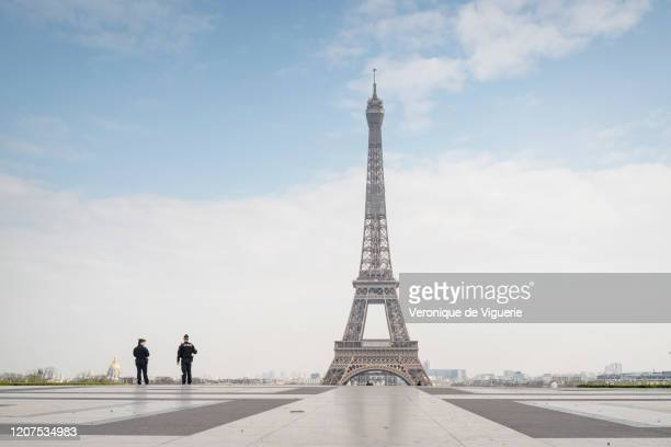 Police officers patrol near the Eiffel Tower during a government enforced quarantine on March 17, 2020 in Paris, France. On March 17, 2020 France...