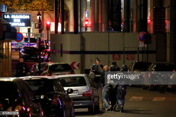 TOPSHOT Police officers patrol near the site of a shooting at the Champs Elysees in Paris on April 20 2017 One police officer was killed and another...