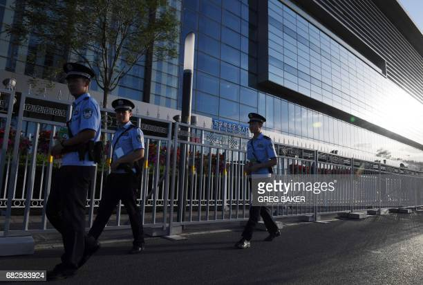 Police officers patrol outside the China National Convention Center the venue for the upcoming Belt and Road Forum in Beijing on May 13 2017 The Belt...