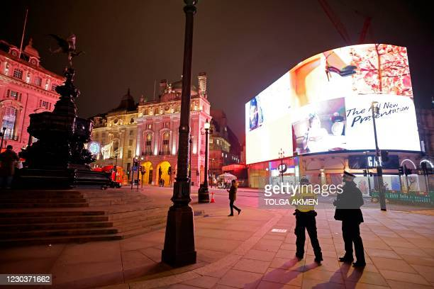 Police officers patrol Piccadilly Circus in a near-deserted London on New Year's Eve, December 31 as authorities in the Tier 4 city hope the message...