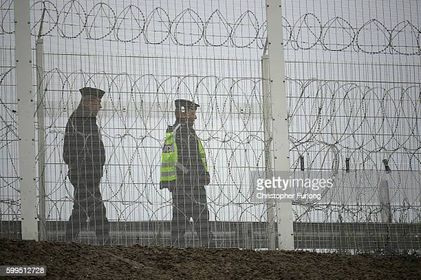 Police officers patrol Security fencing to prevent migrants entering the Port of Calais on September 5 2016 in Calais France Local people and...
